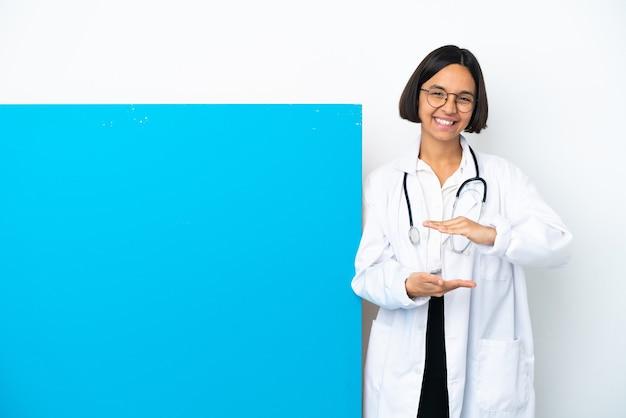 Jeune femme médecin de race mixte avec une grande pancarte isolée tenant un espace de copie imaginaire la paume pour insérer une annonce