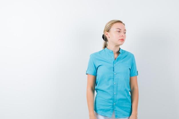 Jeune femme médecin regardant loin en uniforme médical, masque et pensif