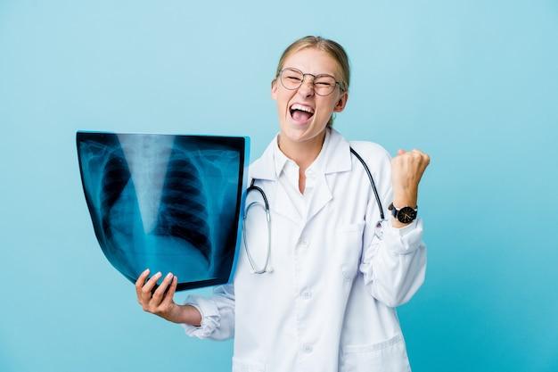 Jeune femme médecin russe tenant une scintigraphie osseuse sur bleu applaudissant insouciant et excité. concept de victoire.