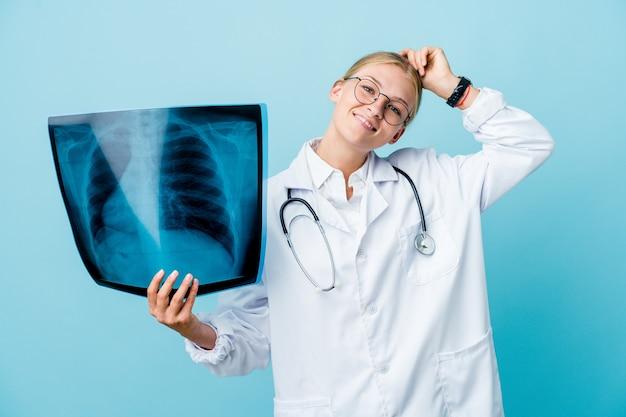 Jeune femme médecin russe tenant une scintigraphie osseuse sur les bras d'étirement bleu