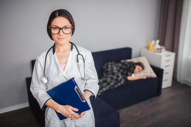 Jeune femme médecin se tenir debout dans la chambre et regarder la caméra. elle tient le comprimé de plastice dans les mains et le stéthoscope autour du cou. petite fille malade dort sur le canapé derrière.