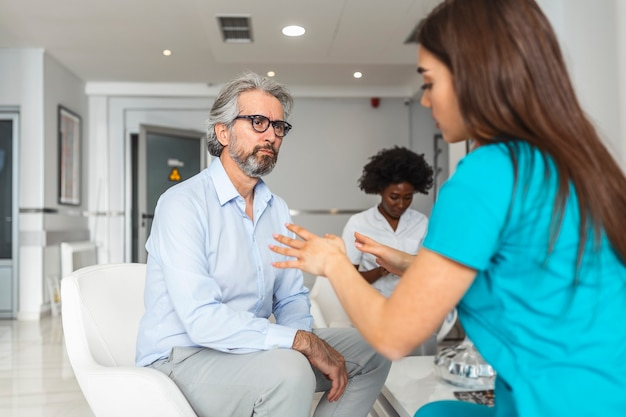 Jeune femme médecin et senior man communiquant dans une salle d'attente à l'hôpital.
