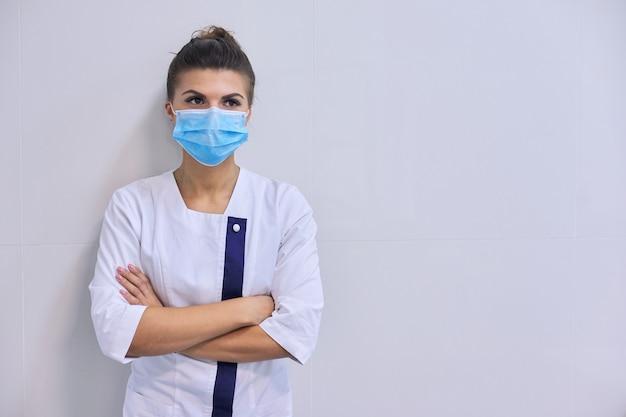 Jeune femme médecin sérieuse confiante en masque médical avec les bras croisés, mur de fond à l'hôpital, espace copie