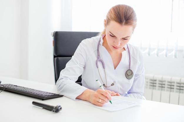 Jeune femme médecin souriante blonde assise au bureau avec un stylo et un stéthoscope au cou