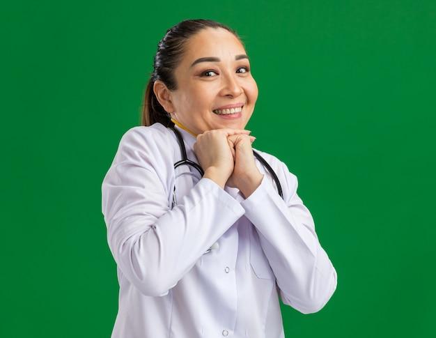 Jeune femme médecin avec un sourire timide sur le visage en attente de surprise, main dans la main
