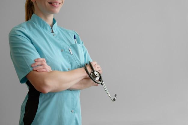 Jeune femme médecin avec stéthoscope isolé sur gris