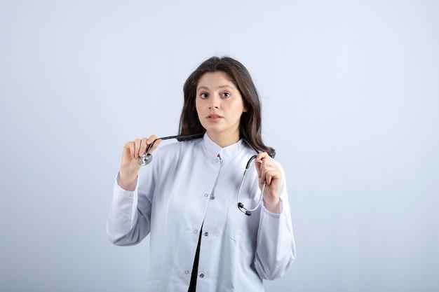 Jeune femme médecin avec stéthoscope posant contre un mur blanc.
