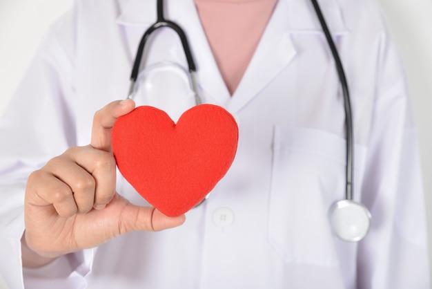 Jeune femme médecin avec stéthoscope tenant un coeur rouge à la main sur blanc