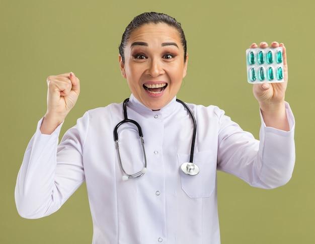 Jeune femme médecin tenant une ampoule avec des pilules serrant le poing heureux et excité