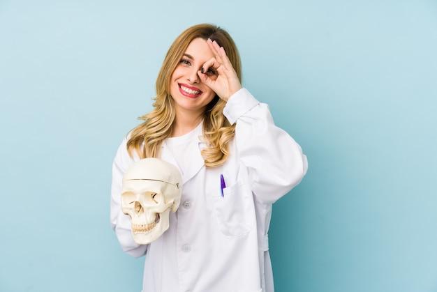 Jeune femme médecin tenant un crâne excité en gardant le geste ok sur les yeux.