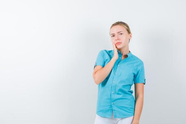 Jeune femme médecin tenant la main sur la joue en uniforme médical, masque et à la réflexion