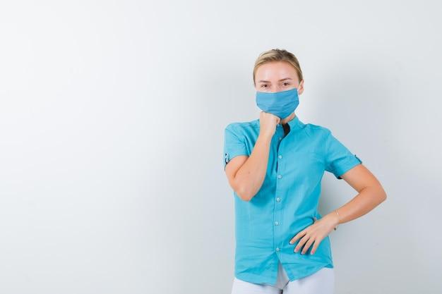 Jeune femme médecin tenant la main sur le menton tout en gardant la main sur la hanche en uniforme médical