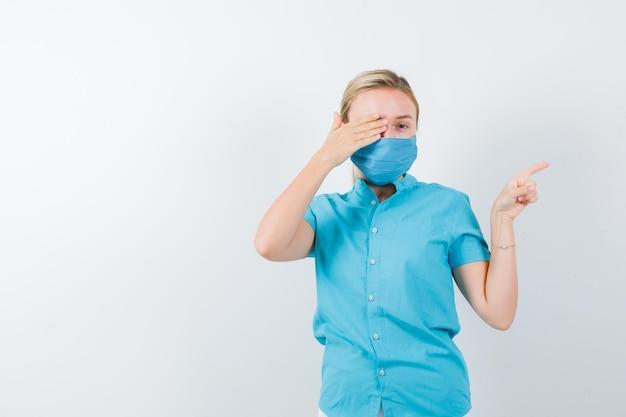 Jeune femme médecin tenant la main sur l'œil tout en pointant vers le côté droit isolé