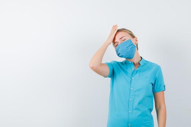 Jeune femme médecin tenant la main sur la tête en uniforme et à la fatigue isolée