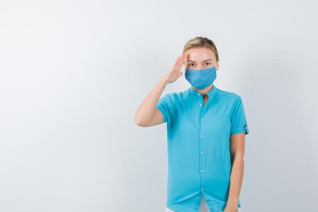 Jeune femme médecin tenant la main sur la tête en uniforme médical, masque et l'air confiant