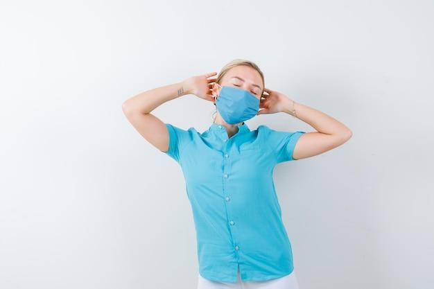 Jeune femme médecin tenant les mains sur la tête en uniforme médical, masque et l'air confiant