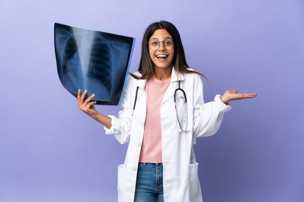 Jeune femme médecin tenant une radiographie avec une expression faciale choquée