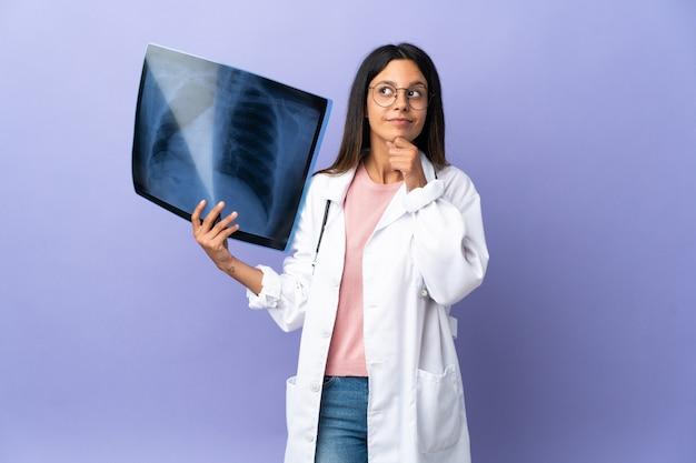 Jeune femme médecin tenant une radiographie et en levant