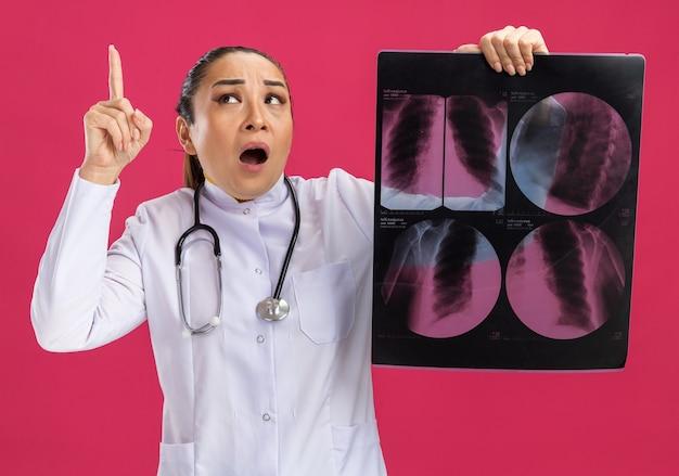 Jeune femme médecin tenant une radiographie des poumons jusqu'à surpris montrant l'index ayant une nouvelle idée