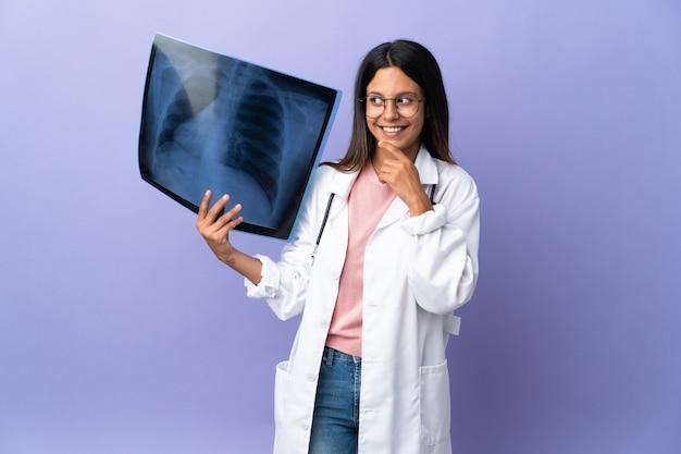 Jeune femme médecin tenant une radiographie en regardant en souriant