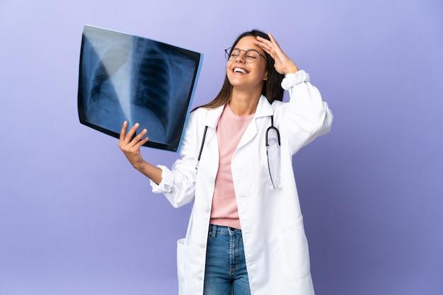 Jeune femme médecin tenant une radiographie souriant beaucoup