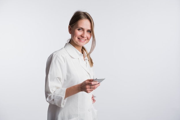 Jeune femme médecin tenant son smartphone tout en souriant à la caméra