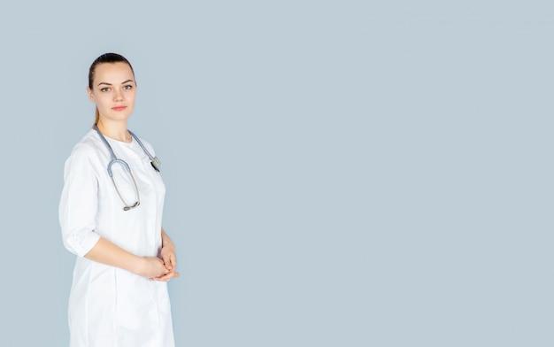 Jeune femme médecin en uniforme blanc avec phonendoscope sur son cou