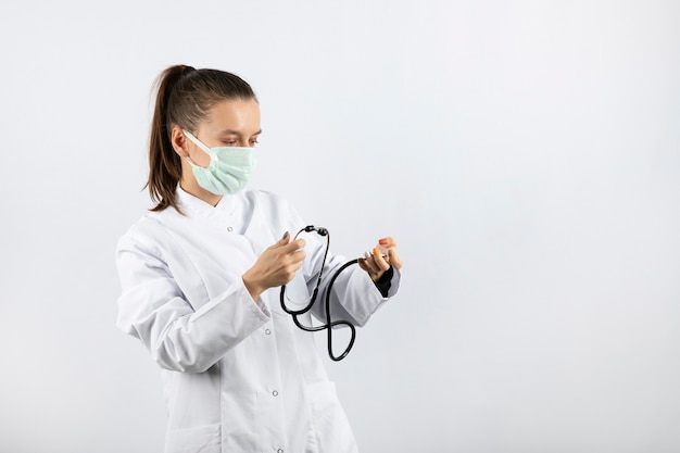 Jeune femme médecin en uniforme blanc regardant un stéthoscope