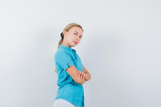 Jeune femme médecin en uniforme médical, masque debout avec les bras croisés