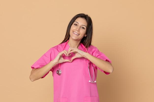 Jeune femme médecin avec un uniforme rose gesticulant sur mur brun