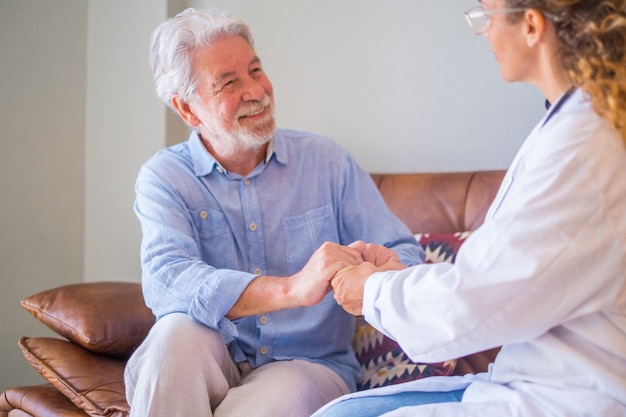 Jeune femme médecin vérifiant et aidant un homme âgé à son domicile. médecin aidant un patient âgé et prodiguant des soins, assis sur un canapé. femme soignante à domicile avec un vieil homme à la retraite à la maison