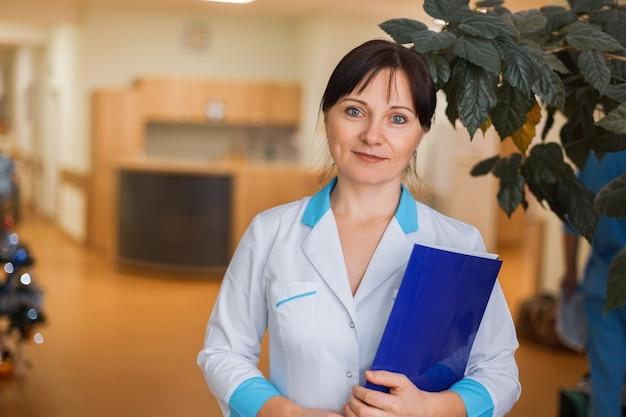 Jeune femme médecin en vêtements blancs médicaux avec un dossier pour les documents debout à l'hôpital.