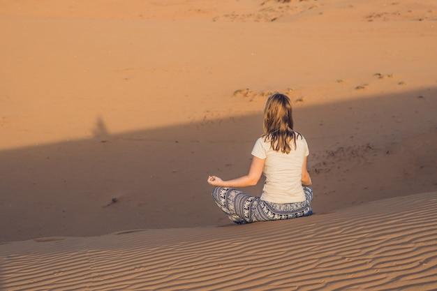 Jeune femme méditant dans le désert de sable rad au coucher du soleil ou à l'aube