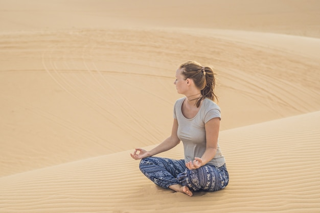 Jeune femme méditant dans le désert, vietnam