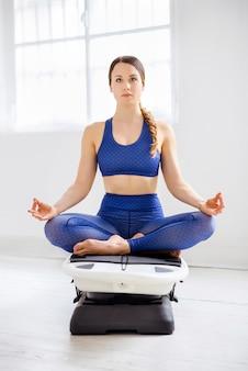 Jeune femme méditant dans la position du lotus sur un surfset dans une salle de sport high key