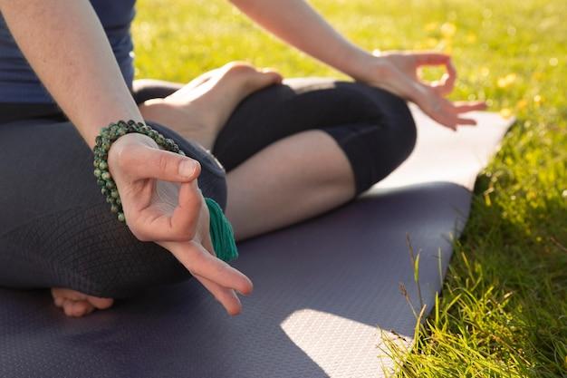 Jeune Femme Méditant à L'extérieur Sur Un Tapis De Yoga Photo gratuit