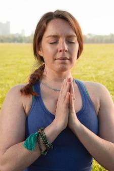 Jeune femme méditant à l'extérieur