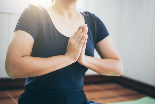 Jeune femme méditation tout en pratiquant le yoga intdoor. femme exerçant vital et méditation pour le mode de vie de remise en forme concept de yoga et de santé, calme et détente