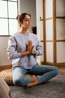 Jeune femme, méditer, chez soi