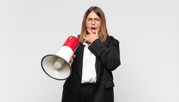 Jeune femme avec un mégaphone avec la bouche et les yeux grands ouverts et la main sur le menton