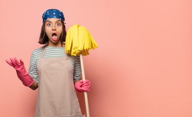Jeune femme de ménage bouche bée et étonnée, choquée et étonnée par une incroyable surprise