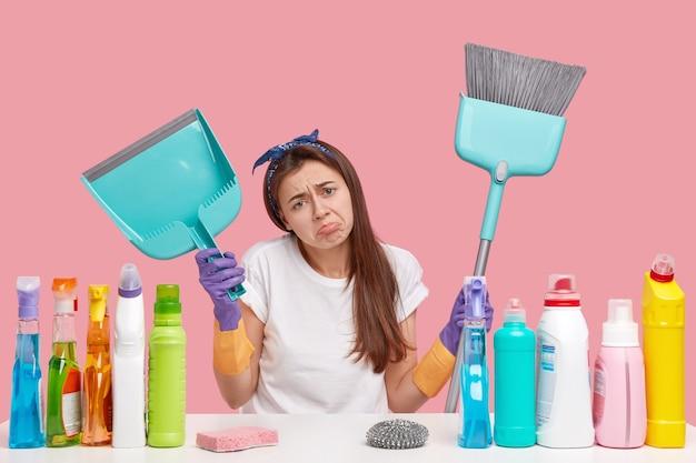 Une jeune femme de ménage bouleversée fronce les sourcils de mécontentement, tient une pelle et un balai, fait le nettoyage