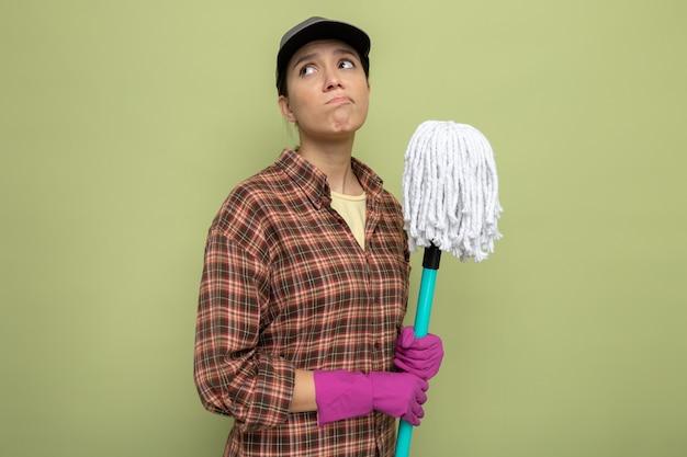 Jeune femme de ménage en chemise à carreaux et casquette dans des gants en caoutchouc tenant une vadrouille levant confuse debout sur un mur vert