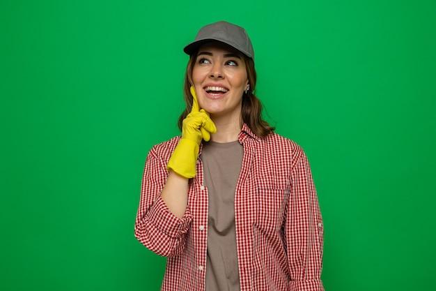 Jeune femme de ménage en chemise à carreaux et casquette portant des gants en caoutchouc levant souriant joyeusement rêvant debout sur fond vert