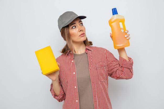 Jeune femme de ménage en chemise à carreaux et casquette tenant une bouteille de produits de nettoyage et une éponge à la confusion ayant des doutes debout sur fond blanc