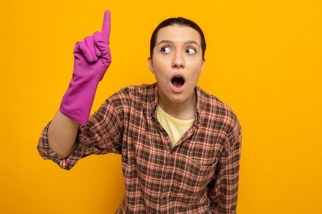 Jeune femme de ménage en chemise à carreaux dans des gants en caoutchouc, l'air intriguée et surprise montrant l'index avec la bouche grande ouverte debout sur le mur orange