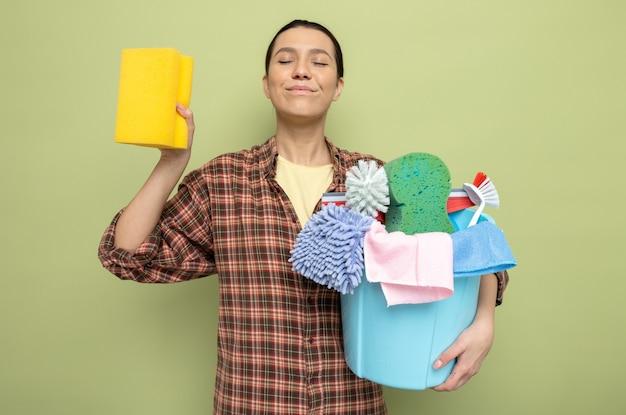Jeune femme de ménage en chemise à carreaux tenant un seau avec des outils de nettoyage et une éponge souriante heureuse et positive debout sur un mur vert