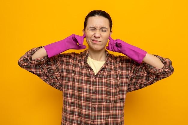 Jeune femme de ménage dans des vêtements décontractés dans des gants en caoutchouc à la recherche d'oreilles mal fermées avec les doigts avec une expression agacée debout sur un mur orange
