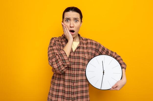 Jeune femme de ménage dans des vêtements décontractés tenant une horloge à l'air étonné et choqué