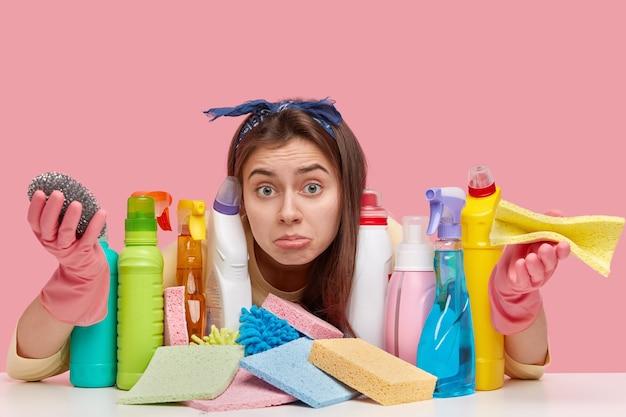 Jeune femme de ménage désemparée européenne regarde avec apathie à la caméra, répand les paumes, porte des gants de protection, porte un chiffon